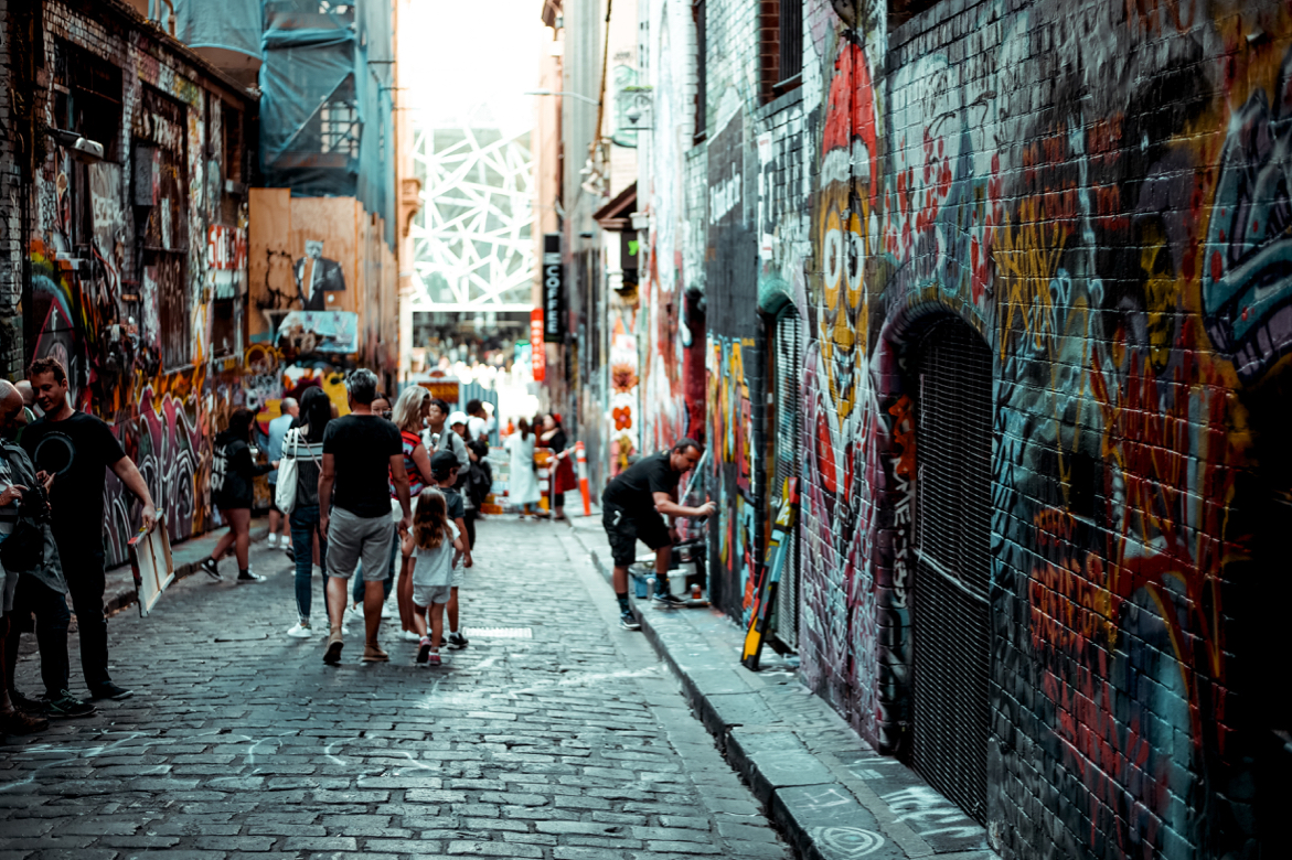 People drawing graffiti on walls in a lane in Melbourbe, Australia.