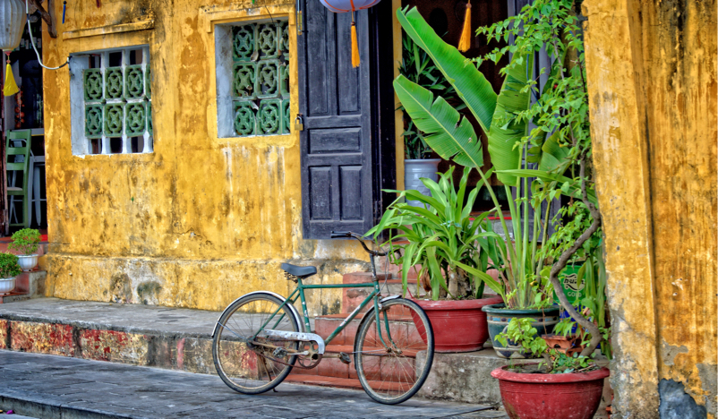 Bicycle parked at a yellow house in Vietnam
